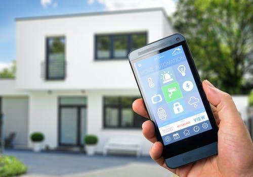 Smarthome App wird vor dem Haus auf dem Smartphone bedient