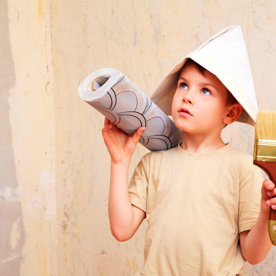Kind beim tapezieren