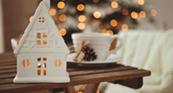 Weißes Teelichthaus vor Weihnachtsbaum