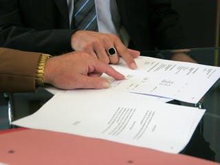 Zwei Menschen prüfen einen Kaufvertrag