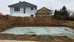 Ausgehobene Baugrube für Hausbau mit Plane bedeckt