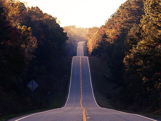 Gerader Straßenverlauf in hügeliger Landschaft