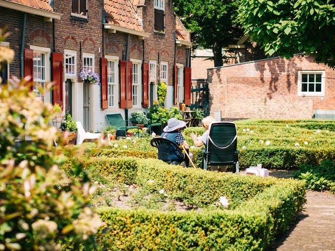 Altes Ehepaar sitzt im Garten vor eigenem Haus