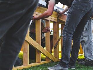 Personen bauen Zaun auf