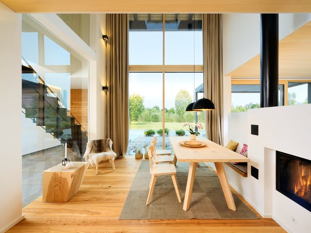 Großer Wohnbereich mit Kamin im modernen Alpenhausstil