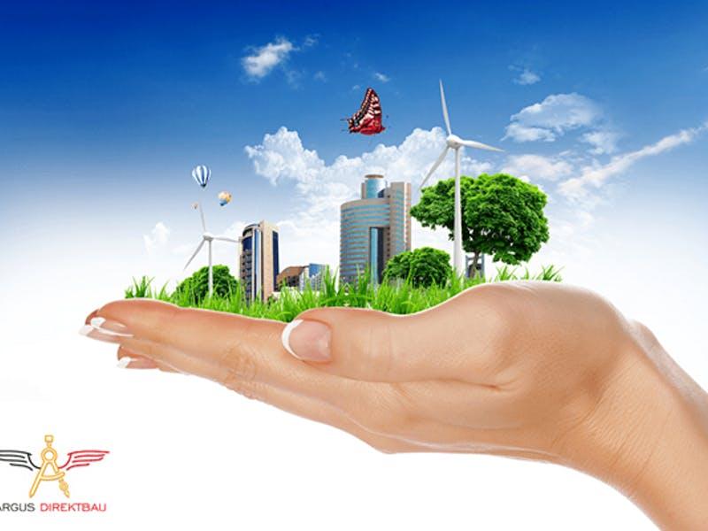 Hand hält Gebäude, Windräder und Bäume