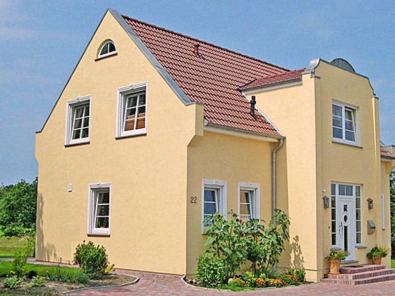Gelbes Einfamilienhaus von AThoden Bau