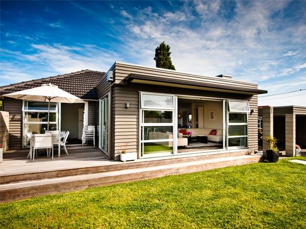 Holzbungalow mit Terrasse und Sonnenschirm