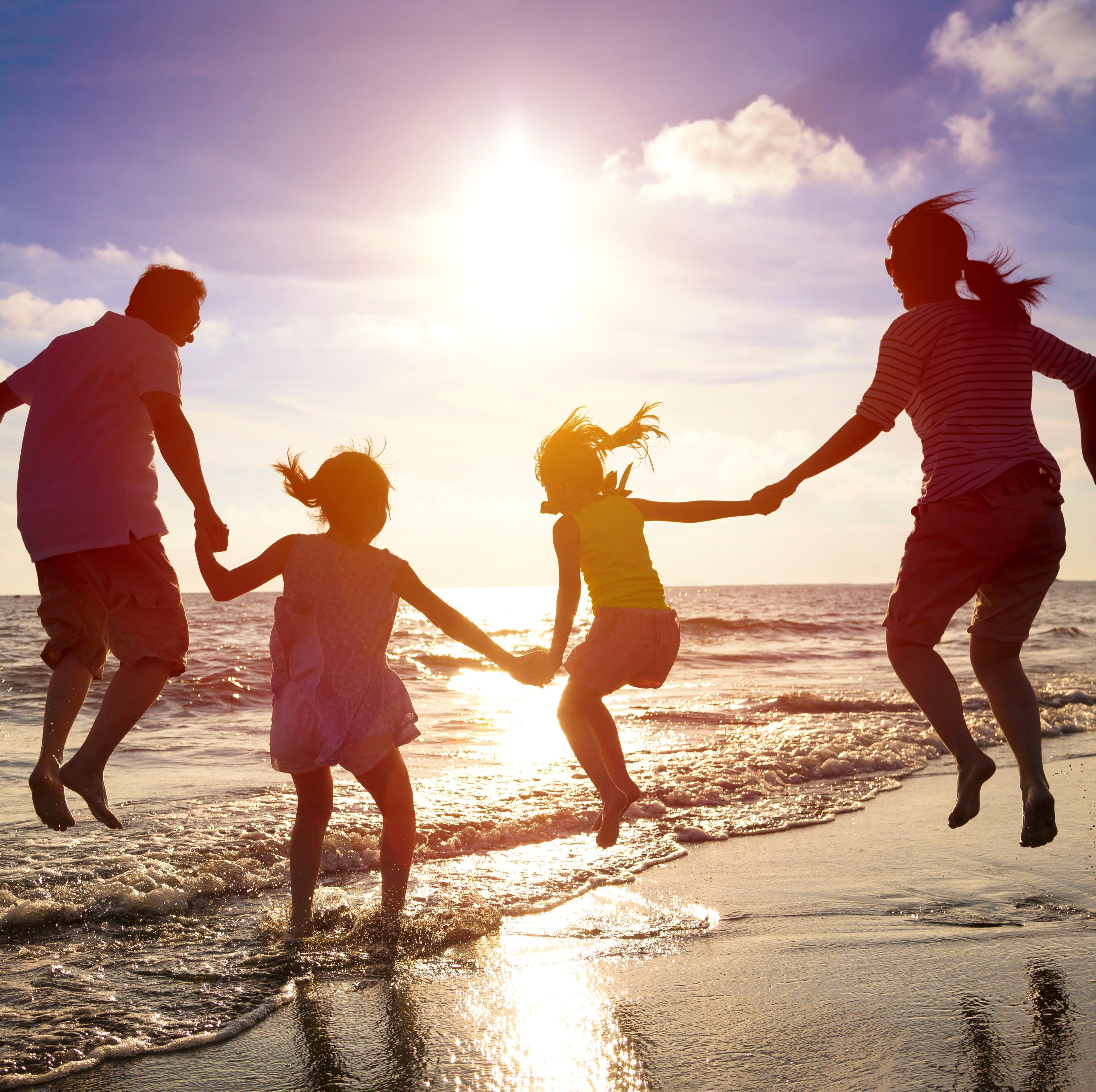 Familie springt am Strand