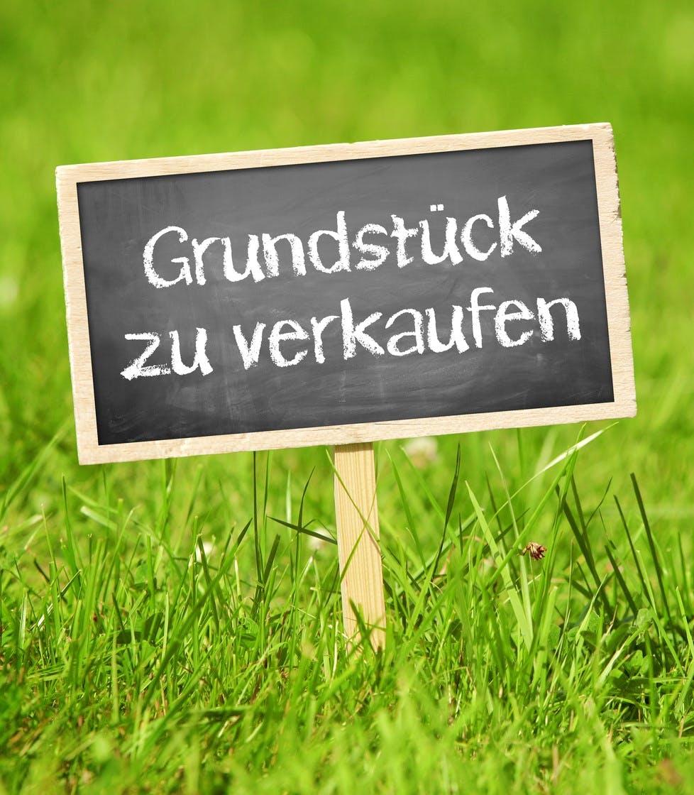 Grundstück zu verkaufen Schild auf Rasen