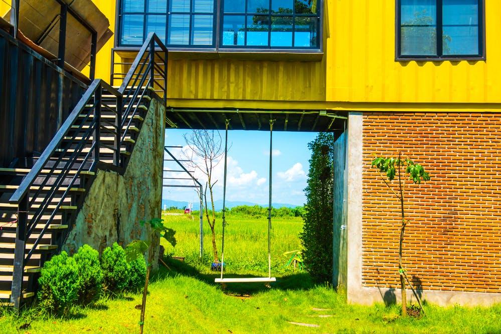 Gelbes Containerhaus mit Treppe und Schaukel
