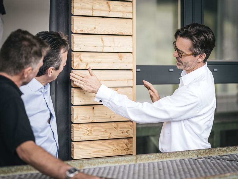 Person erklärt Holzfassade bei Griffnerhaus