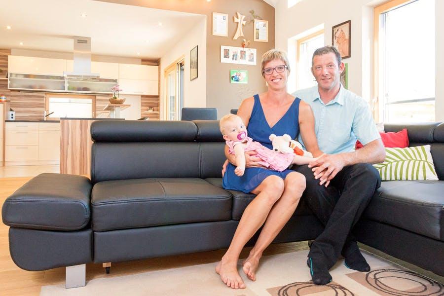 Familie sitzt auf schwarzem Ledersofa im Wohnbereich