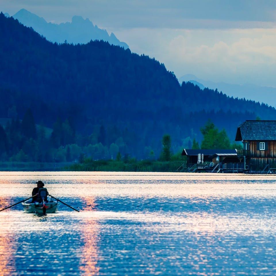 Einsames Holzhaus am See mit einem Ruderboot im Vordergrund