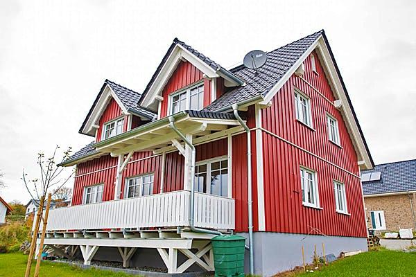 Einfamilienhaus mit roter Holzfassade von Hausbau Heggemann