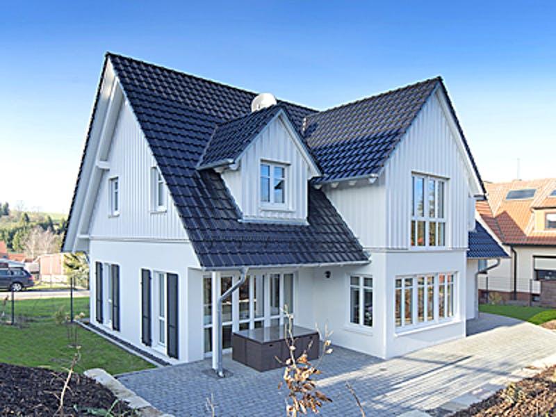 Weißes Holzhaus mit spitzem Satteldach
