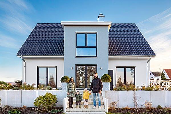 Das Bild zeigt ein Kundenhaus mit der Familie im Vordergrund