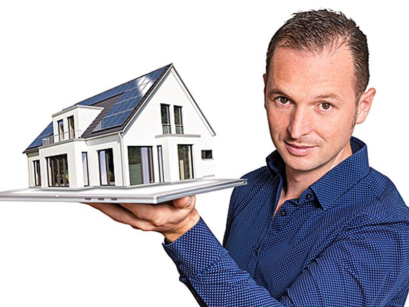 Mann hält Hausmodell in einer Hand