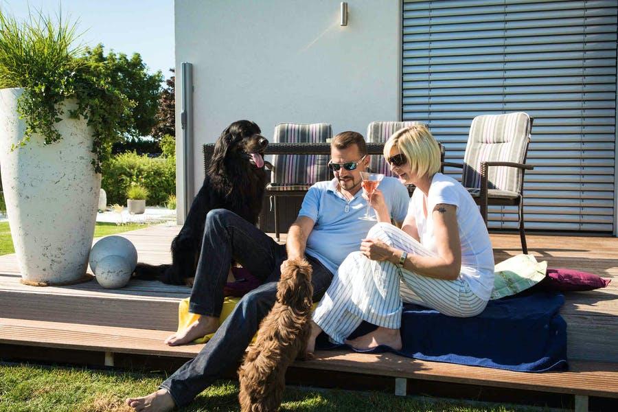 Paar sitzt mit seinen beiden Hunden vor ihrem neuen VARIO-HAUS