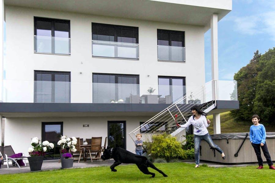 Familie spielt vor ihrem weißen VARIO-HAUS mit einem schwarzen Hund