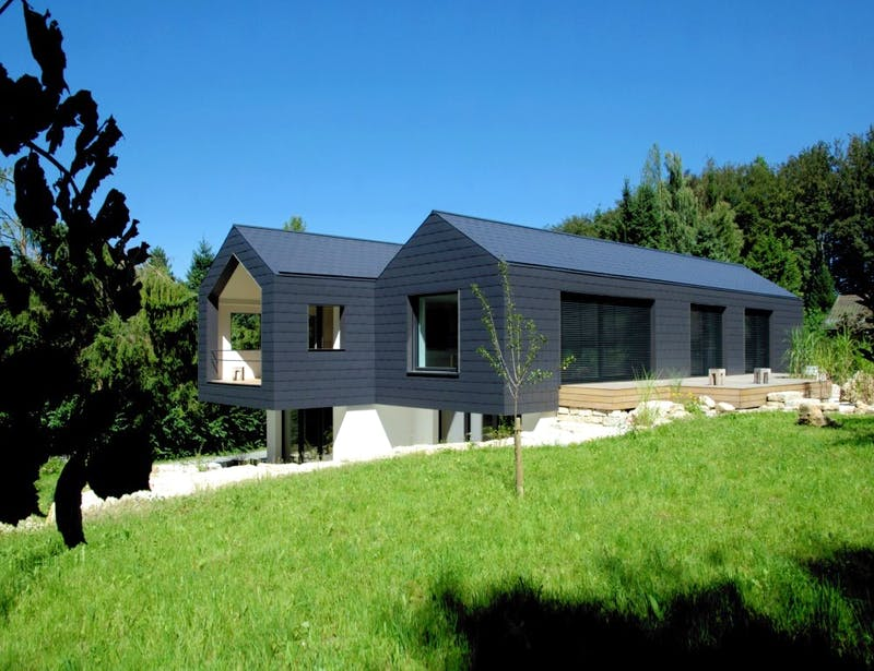 Architektenhaus mit zwei Dachgiebeln und Satteldächern mit schwarzer Fassade