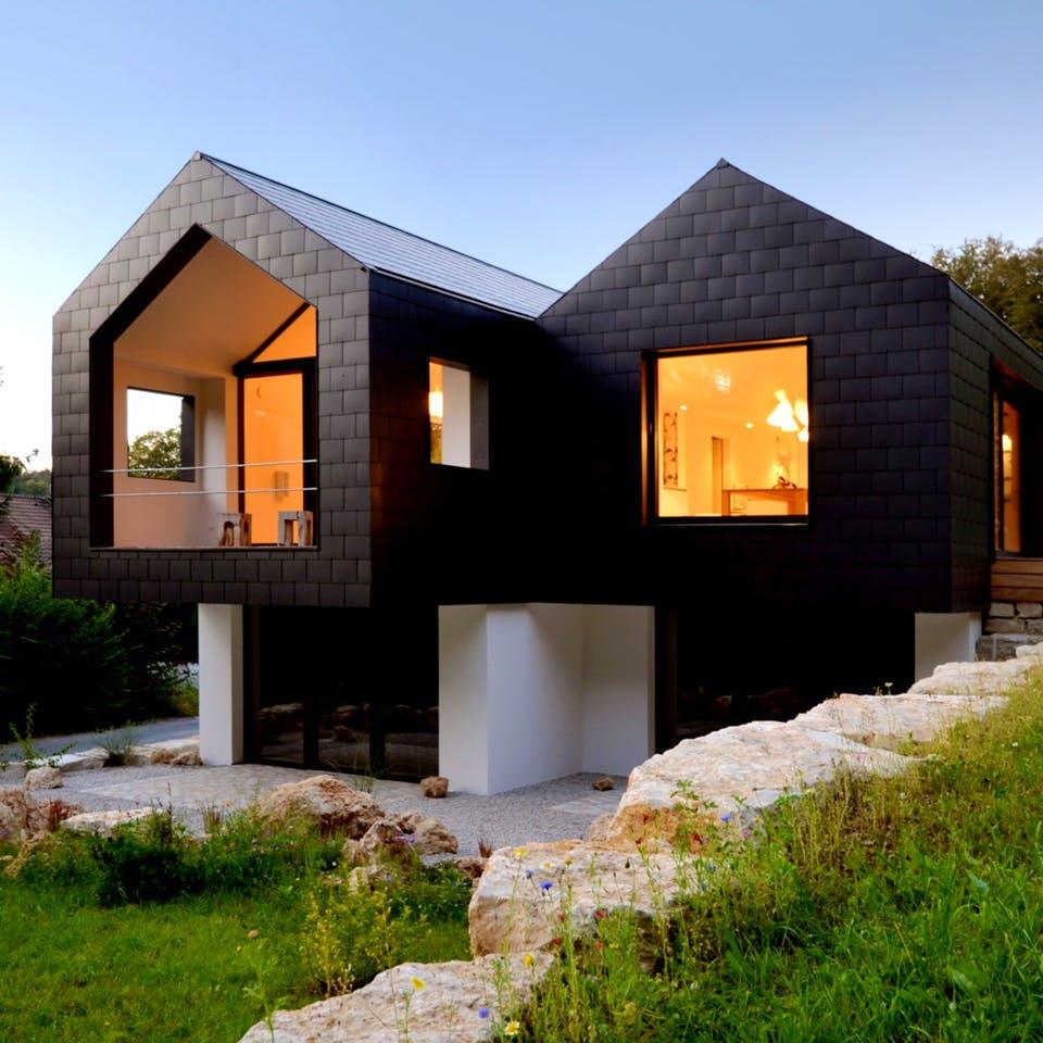 Ein schwarz verkleidetes Architektenhaus mit doppeltem Satteldach