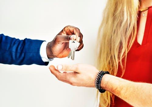Eine Person übergibt einer anderen Person einen Schlüssel