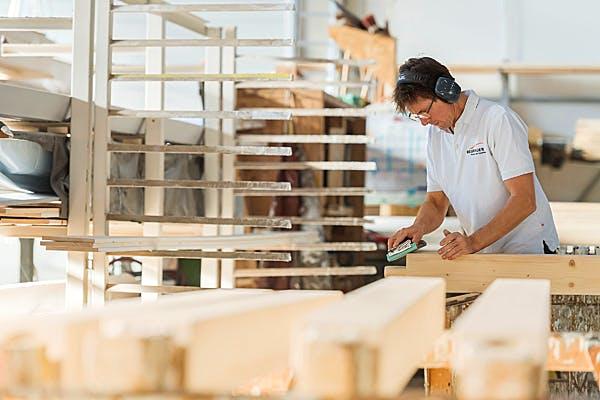 Mitarbeiter von Regnauer Vitalhäuser bearbeitet Holz