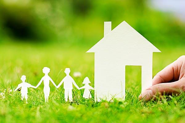 Haus und Familie aus Papier auf Wiese