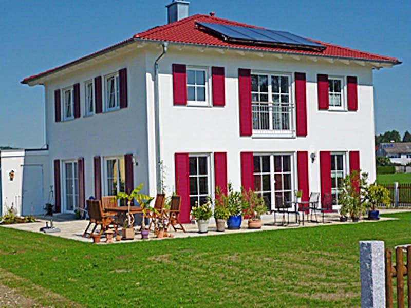 Weiße Stadtvilla mit roten Fensterläden von Rothdach