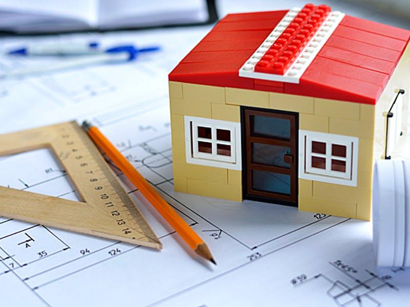 Hausmodell, Bleistift und Lineal auf einem Bauplan