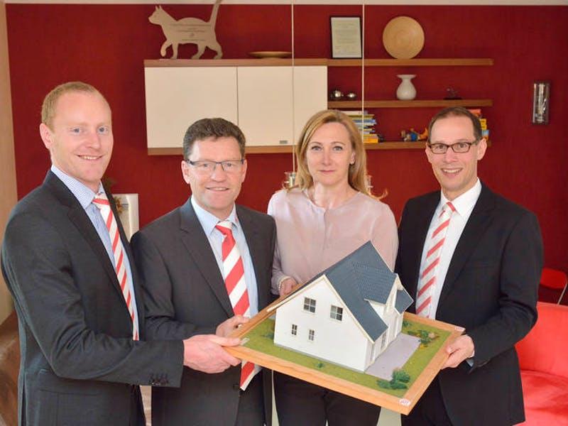 4 Personen halten zusammen ein Hausmodell in den Händen