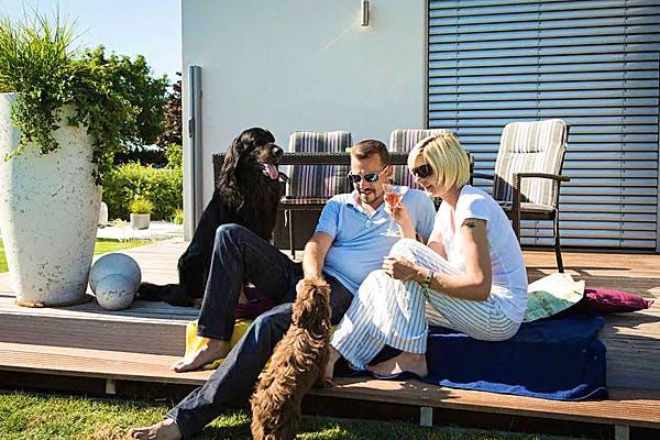 Mann und Frau mit 2 Hunden auf der Terrasse
