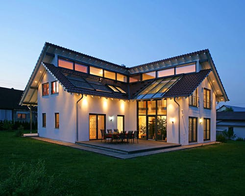 Beleuchtetes Haus mit versetztem Pultdach im dunkeln