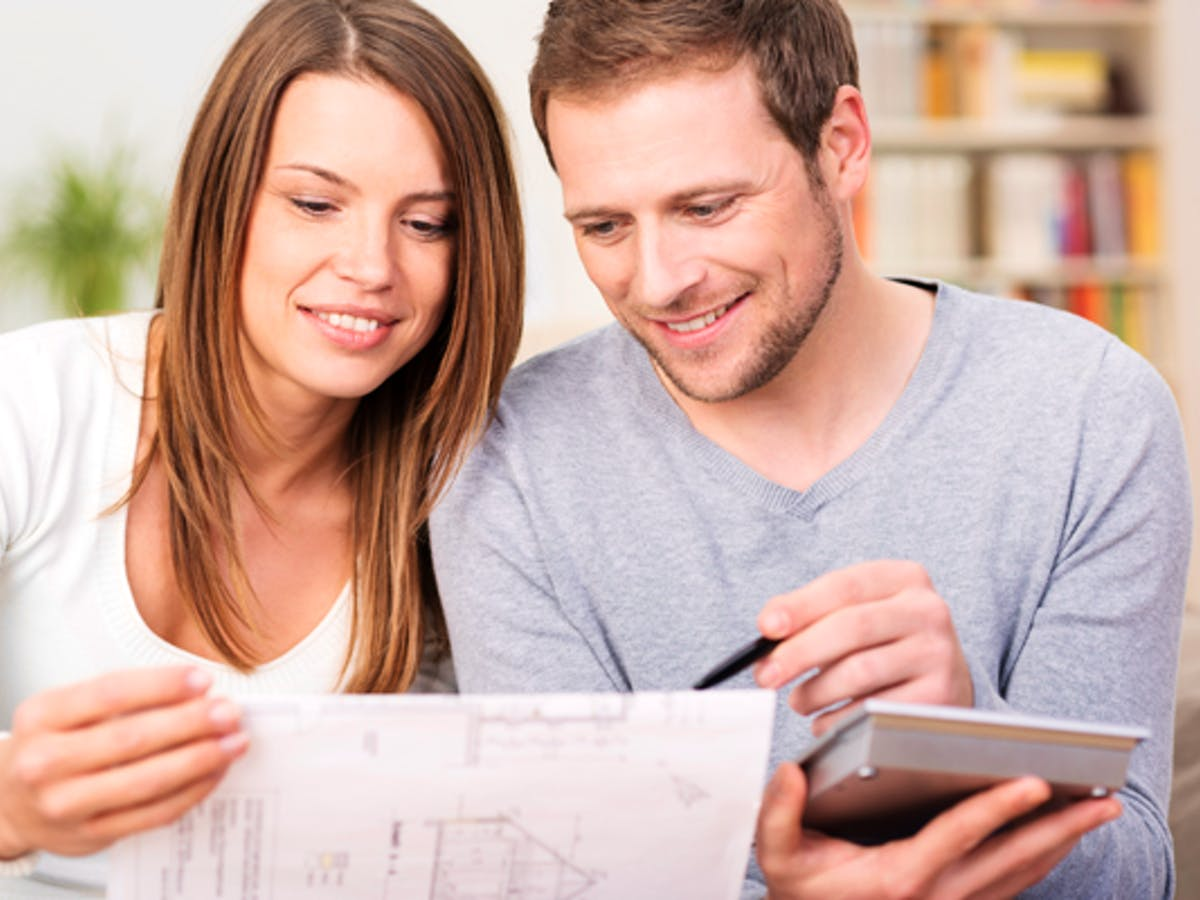 Junges Paar studiert den Bauplan ihres Hauses