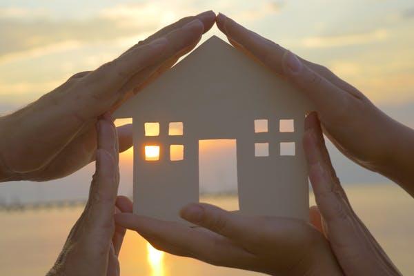 Mehrere Hände halten die Schablone eines Haus vor einen Sonnenuntergang