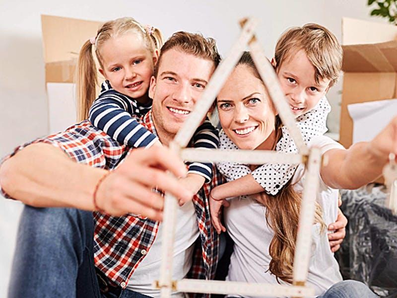 Junge Familie mit Zollstock und Schlüssel