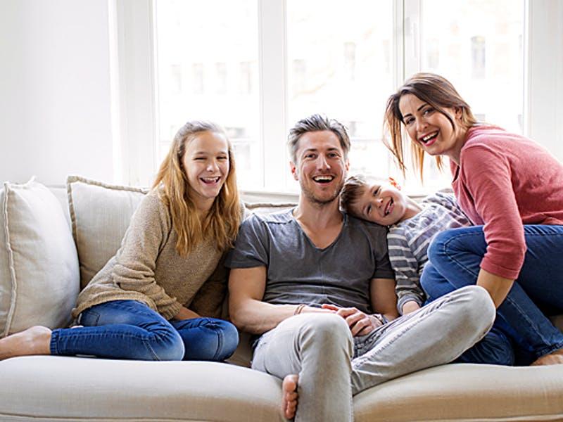 Familie sitzt auf einem Sofa